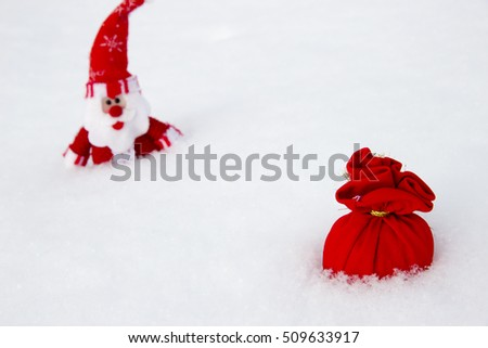 Toy Santa Claus with red bag of gifts on the snow