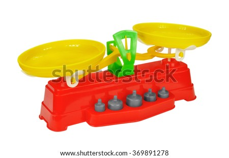Toy scales with weights of colored plastic against white background - stock photo