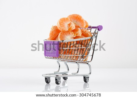 Toy shopping cart filled with mandarin slices - healthy food concept