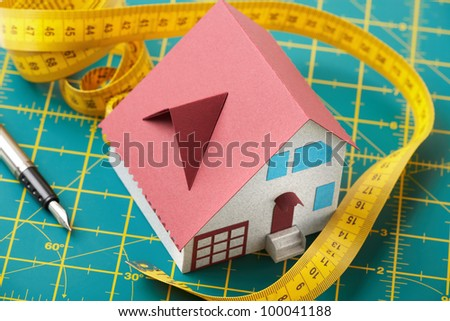 Toy small house on green graph background with pen and measuring tape. - stock photo