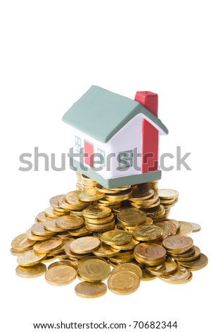 Toy small house standing on a heap of coins. The concept of purchase of habitation