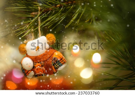 Toy Snowman In The Warm Clothing on The Christmas Tree and Decoration Candle Light - stock photo