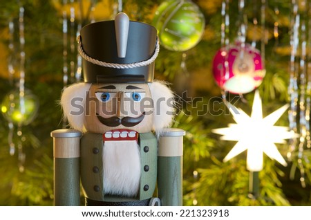Toy soldier wooden nutcracker statue standing in front of decorated Christmas tree - stock photo