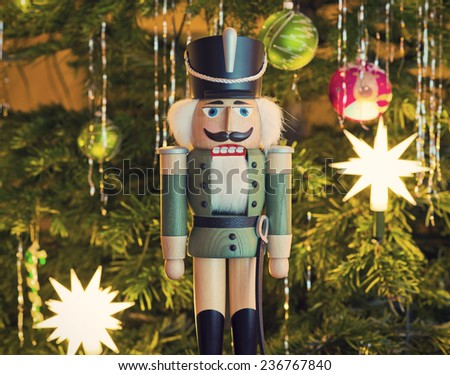 Toy soldier wooden nutcracker statue standing in front of decorated Christmas tree, vintage style  - stock photo