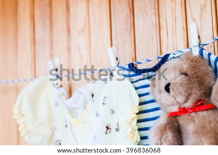 Toy teddy bear with baby clothing. Clean little child cloth hanging on rope in laundry. Blue cotton infant dry brown small toy. Birth newborn kid.   - stock photo