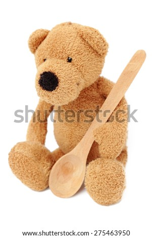 Toy teddy bear with wooden spoon isolated