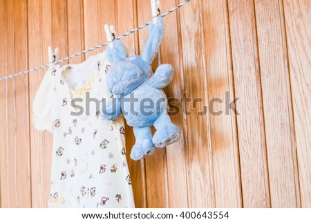 Toy teddy dog, puppy with baby clothing. Clean little child cloth hanging on rope in loundry. Blue cotton infant dry brown small toy. Birth newborn kid.