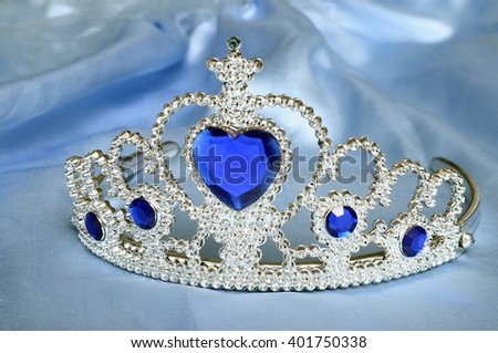 Toy tiara with diamonds and blue gem, like a princess crown, on blue satin tissue - stock photo
