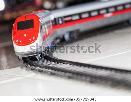 Toy train over railway, dynamic diagonal image, horizontal
