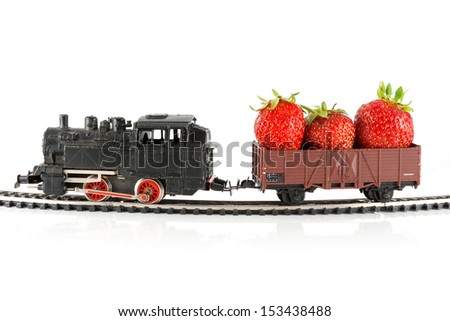 Toy train pulling carriage with strawberries - stock photo