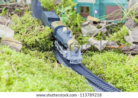 Toy train running through the forest moss - stock photo