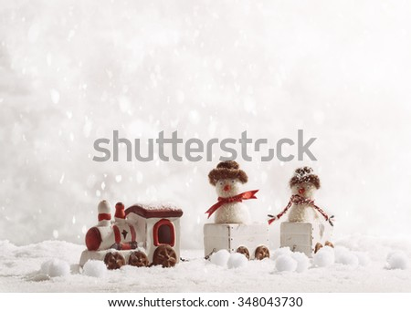 Toy train set carrying snowmen in winter setting - stock photo