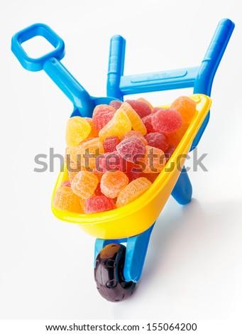 toy wheelbarrow full of sugary jellies - stock photo