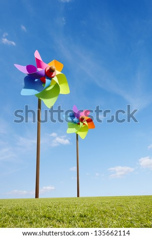 Toy windmill concept of green energy wind farm in field - stock photo