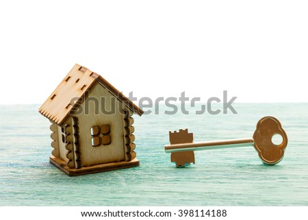 toy wooden model house as symbol family and love concept  on sunny old blue wooden background buying a house, mortgage, repair, stability, the keys  - stock photo