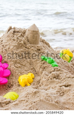 Toys and sand with sea background. - stock photo
