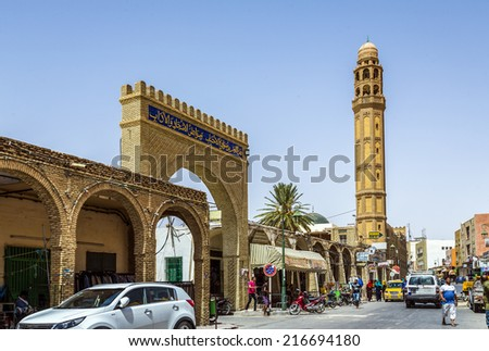 TOZEUR, TUNISIA - AUGUST 18, 2014: The el-Ferdous Mosque built with bricks ocher whose peculiar placement form geometrical designs that decorate the entire facade. Its towering minaret of 7 bodies. - stock photo