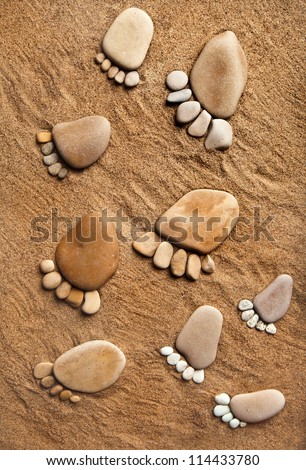 trace bare feet walking made of pebble stones on the beach sand background - stock photo