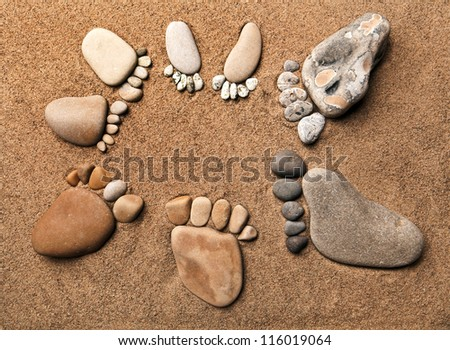 trace feet of a pebble stone on the sea sand backdrop , concept happy family - stock photo