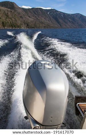 Trace motor boats on the water of a mountain lake. Outboard motor on the boat. - stock photo