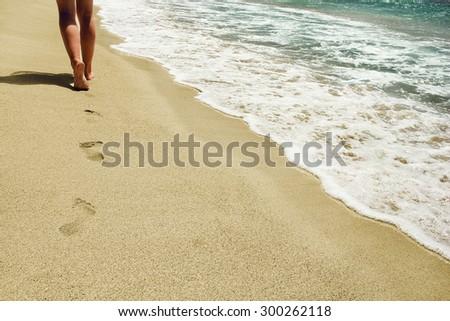 trace their feet on the sand near the sea - stock photo