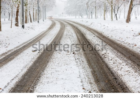 Traces of car tires on the street during heavy snowstorm, tracks visible and the road still not cleaned, presenting danger for drivers -  accident waiting to happen - stock photo