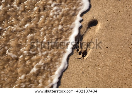 Traces of feet in the sand on the beach - stock photo