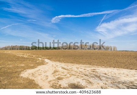 Traces of torrents of spring on a field - stock photo