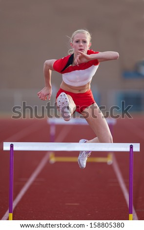 Track and field athlete jumps over hurdles. - stock photo