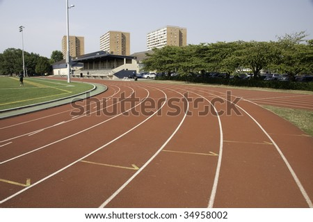Track and field lanes in a stadium.This is the a turn coming up. - stock photo