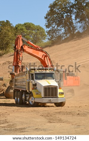 Track hoe excavator filling up a dump truck at  a new commercial construction development