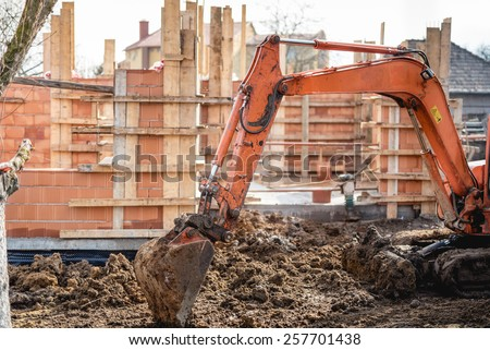 track-type excavator loader working on earth and loading at house construction site - stock photo