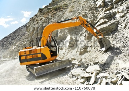 track-type loader excavator machine doing earthmoving roadwork at mountain - stock photo