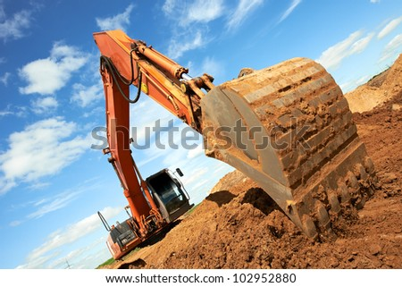 track-type loader excavator machine doing earthmoving work at sand quarry - stock photo