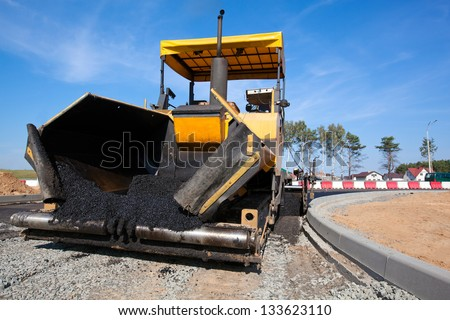 Tracked paver laying fresh asphalt pavement on top of the gravel base during road construction - stock photo