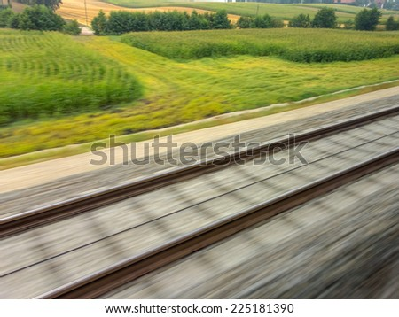 tracks and rails out in motion from a moving train. symbol photo for train ride, tempo and dynamics. - stock photo