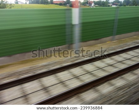 tracks and rails out in motion from a moving train. symbolic photo for train, tempo and dynamics. - stock photo