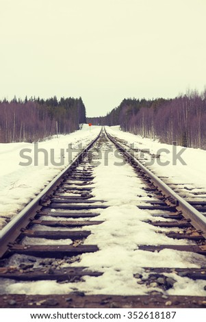 Tracks to far away. Image of an empty railroad track going to far away. Some snow is on the ground. Image taken from a low point of view. Image has a vintage effect applied.