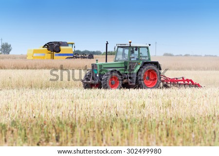 Tractor and combine harvester working in rapeseed field in summer time