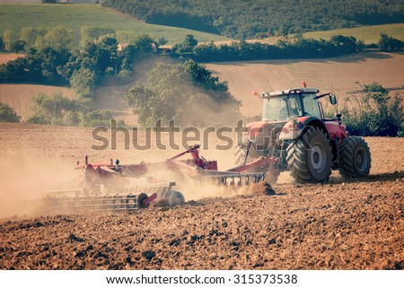 tractor and stubble plow in an harvested field vintrage filtered image - stock photo