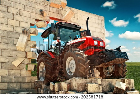 Tractor breaking through wall while preparing land for sowing. Powerful agricultural machinery overcoming all obstacles in farming and agriculture production. - stock photo