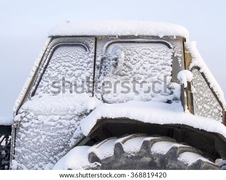 tractor cabin covered with snow - stock photo