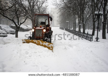 Tractor clearing snow during snowfall