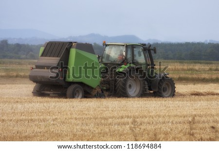 Tractor collecting hay on the summer field. - stock photo