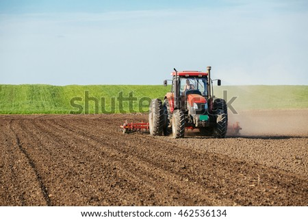 Tractor cultivating field at spring
