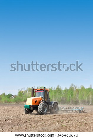Tractor cultivating the field to prepare the soil for seeding plants