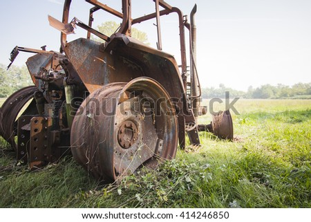 tractor destroyed by fire in agrass field in the summer close up