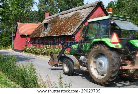 tractor drive past cottage, green agriculture machine and red farm