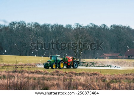 Tractor driving aroung on a field with fertilizer - stock photo