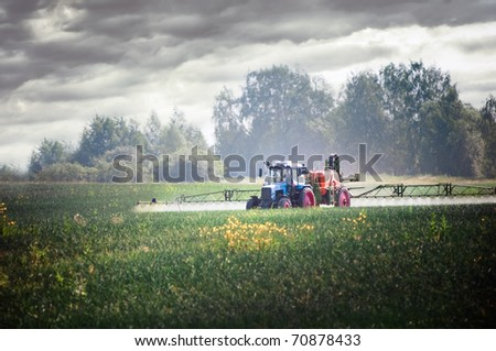 Tractor fertilizes crops in the field - stock photo